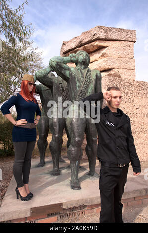 Red haired woman and man in their 20's visit a park that displays old statues of Socialist dictatorial figures at Memento Statue Park,  Budapest - Stock Photo