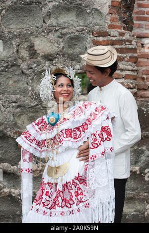 A Panamanian man wearing a traditional mole hugs a woman wearing a pollera, Panama's national costume,  at Panama la Vieja ruins,  Panama City, Panama - Stock Photo