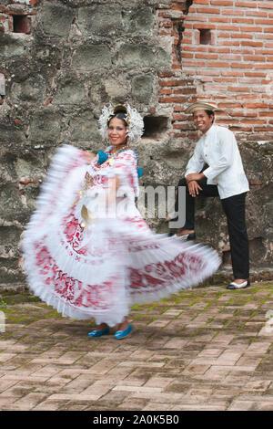 Panamanian woman wearing a pollera, Panama's national costume, dances while a man wearing a traditional mole watches at Panama la Vieja ruins,  Panama - Stock Photo