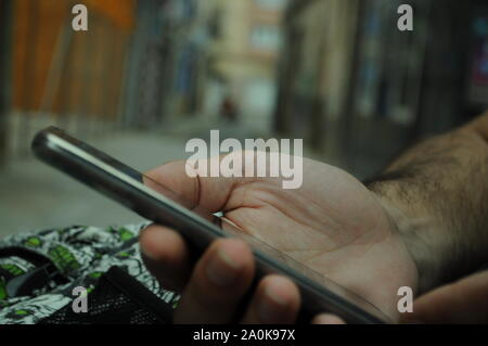 Man hand holding a smartphone in the street and the city out of focus in the background-Man sitting down in a bank in the street using his cellphone - Stock Photo