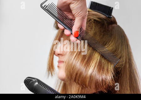 Professional hairdresser straightening long brown hair with hair irons in beauty salon. Close-up