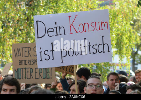 Demonstration during Global Climate Strike with sign saying 'Your consumption is political' in German - Stock Photo