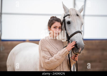 Calm young casual woman in knitted sweater standing by white purebred horse - Stock Photo