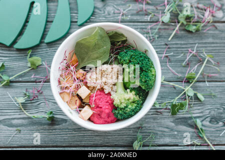 Bowl of bright healthy vegan lunch: vegetable salad with tofu, hummus and broccoli on the wooden table - Stock Photo
