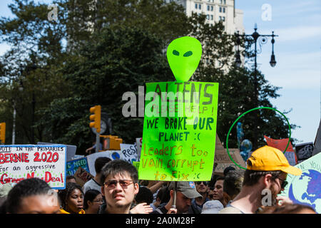 New York, USA. 20th Sep 2019.  Thousands of students as well as adults gathered in New York for the Global Climate Strike, meeting in Foley Square near the Federal Government buildings and New York's City Hall, and marching downtown to Battery Park, where Swedish climate activist and spokesperson Greta Thunberg addressed the crowd. Marchers on Broadway carry signs, one of which reads 'Aliens please help! We broke our planet :( leaders too vain, corrupt, to fix :(' Credit: Ed Lefkowicz/Alamy Live News - Stock Photo