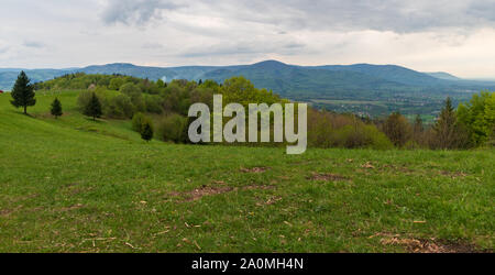 springtime Slezske and Moravskoslezske Beskydy mountains scenery with meadows, trees and hills from place named Dziol above Hradek village in Czech re - Stock Photo