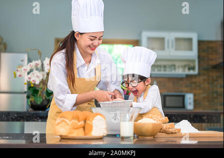 Cute little Asian boy and beautiful mother sifting dough flour with sifter sieve colander in home kitchen on table for prepare to baking bakery and ca - Stock Photo