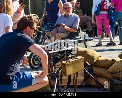EDEGEM, ANTWERP/BELGIUM – 09/15/2019: 75 jaar bevrijding WOII: Close up jonge man die een MG43 machinegeweer van dichtbij bekijkt. - Stock Photo