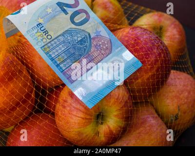 Apple fruit in backet and paper banknote money 20 twenty Euros Euro European Europe - Stock Photo
