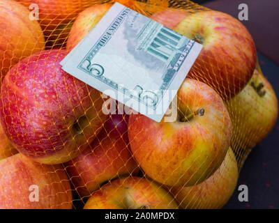 Apple fruit in backet and paper banknote money 5 five Dollars Dollar USA American - Stock Photo