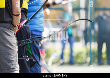 Longbow archer holds modern sport bow with arrow on outdoor sport competition.Professional olympic archers training in shooting targets with bows and