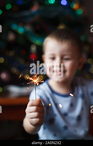 Beautiful Little child holding burning sparkler on New Year's Eve, bengal fire. Select focus on fireworks.