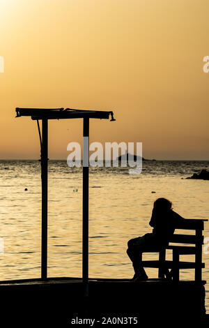 Female silhouette of unrecognizable fit woman sitting on wooden bench at sunset in front of golden Ionian Sea water near beach showers. Colorful dusk as seen from Ksamil, Albania, late spring - Stock Photo