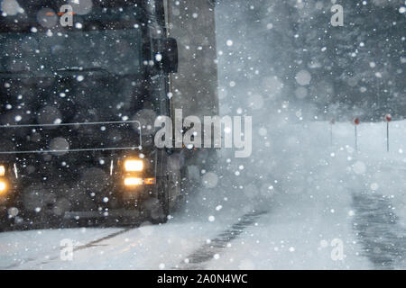 The car is driving on a winter road in a blizzard - Stock Photo