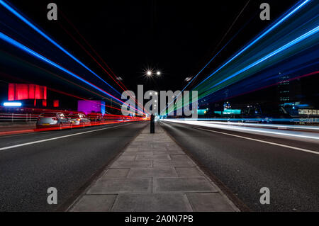 Light trails of traffic on Waterloo bridge at night, London - Stock Photo