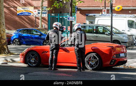 PARIS, FRANCE - SEPTEMBER 18, 2019: Police motorcycle officers controlling a luxury red sports car in a street of Paris. - Stock Photo