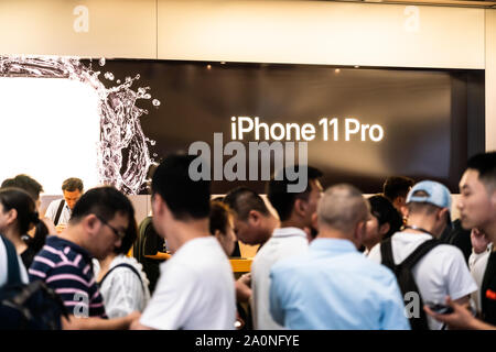 Customers look at the Apple's new iPhone 11 series smartphones at an Apple retail store on East Nanjing Road in Shanghai.Apple launched sales of its latest iPhone 11 series in China. - Stock Photo