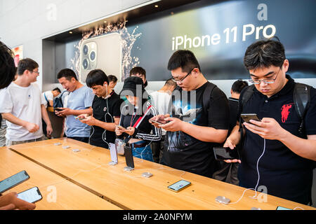 Customers look at the Apple's new iPhone 11 series smartphones in an Apple retail store on East Nanjing Road in Shanghai.Apple launched sales of its latest iPhone 11 series in China. - Stock Photo