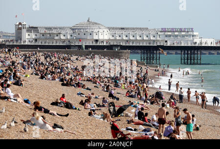 People enjoy the sunshine on the beach in Brighton, East Sussex, as temperatures are expected to soar to 26C in some parts of the country this weekend. - Stock Photo