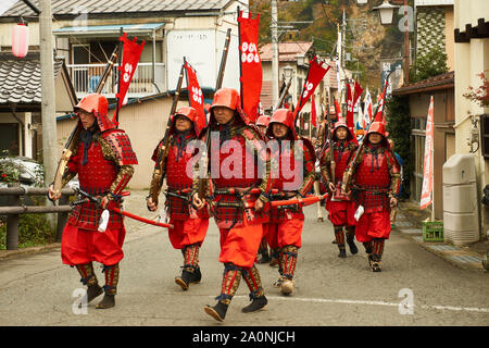 Japanese reenactors dressed in red traditional samurai costume and armour (armor) march during samurai festival in Sarugakyo, Minakami, Gunma, Japan. - Stock Photo