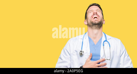 Handsome doctor man wearing medical uniform over isolated background Smiling and laughing hard out loud because funny crazy joke. Happy expression. - Stock Photo
