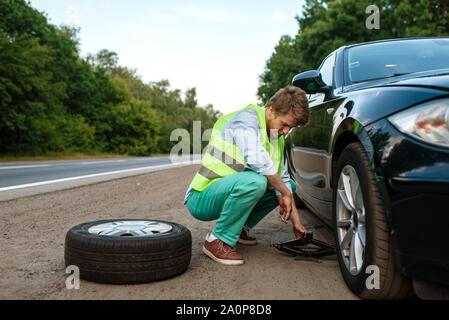 Car breakdown, young man repairing flat tyre - Stock Photo