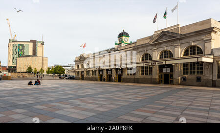 Cardiff, Wales, UK - July 21, 2019: Pedestrians walk through Central Square outside Cardiff's Central Station on a summer evening. - Stock Photo