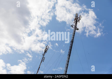 Red and white mobile phone cell tower repeater, with a small microwave dish on blue sky with clouds background, groundview - Stock Photo