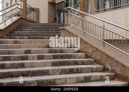 Ground view of concrete tiled concrete stairs with metal rail leading to apartment building - Stock Photo