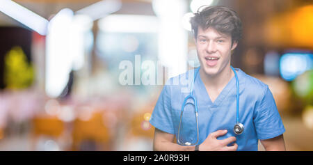 Young doctor wearing medical uniform over isolated background Smiling and laughing hard out loud because funny crazy joke. Happy expression. - Stock Photo