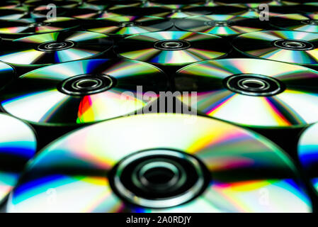 CDs / DVDs lying on a black background with colorful reflections of light. - Stock Photo