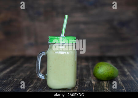 Fresh green smoothie from avocado, banana and honey in glass mug on wooden background, close up. Concept of healthy eating - Stock Photo