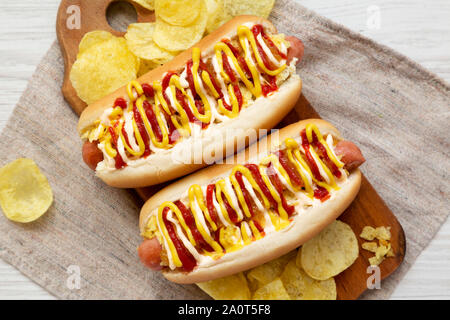 Homemade colombian hot dogs with pineapple sauce, yellow mustard and mayo ketchup on a rustic wooden board, top view. Flat lay, from above, overhead. - Stock Photo