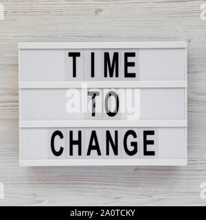 'Time to change' words on a modern board over white wooden table, top view. Overhead, from above. Flat lay. - Stock Photo