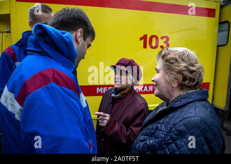 A team of medical emergency doctors talk with old women in the background of an ambulance in Moscow, Russia - Stock Photo