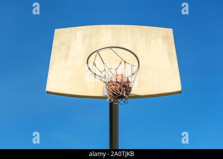 Basketball flies into the basketball ring. - Stock Photo