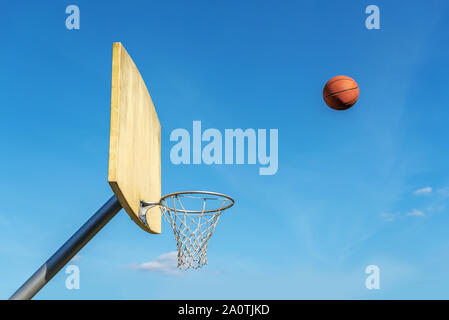 Basketball flies into the basketball ring. - Stock Photo