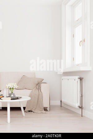 Mock up wall with beige white sofa, two tables and a chair in modern interior background, living room with large window an radiator, Scandinavian styl - Stock Photo
