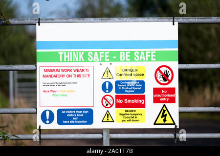 Construction site health and safety message rules sign board signage on fence boundary - Stock Photo