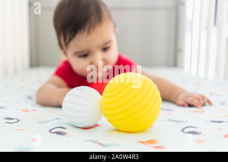 Baby playing with colorful toy rubber balls in the crib in a bright room. Child wearing a red bodysuit, laying on playful dinosaur crib sheet. - Stock Photo