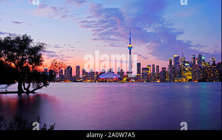 Toronto waterfront syline at dusk, CN Tower in blue and yellow lighting. - Stock Photo