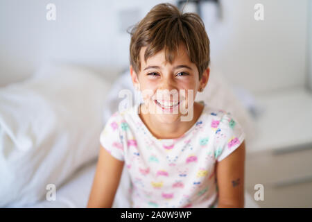 Little girl, eight years old, lying on her bed - Stock Photo