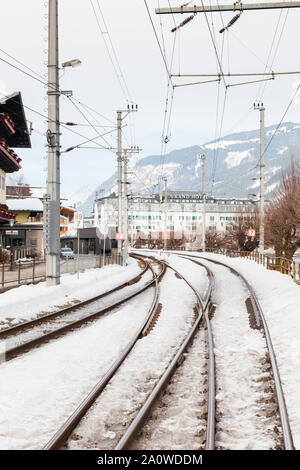 The view along a snow covered railway track in the town of Zell am See, Austria.  In the background can be seen the Grand Hotel. - Stock Photo