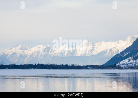 The view from the Austrian town of Zell am See across Lake Zell towards a winter landscape. - Stock Photo