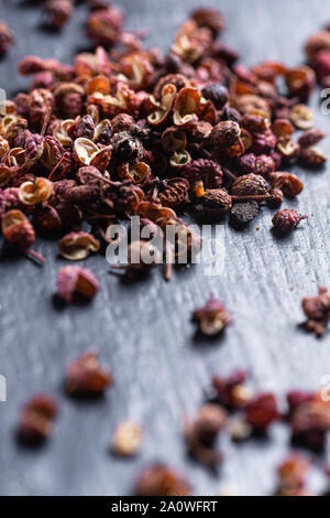 Sichuan peppercorns on black background - Stock Photo