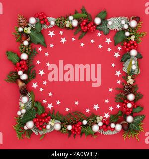 Christmas and winter background border with star and bauble decorations and a variety of flora and fauna on red background with copy space. - Stock Photo