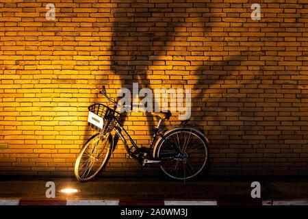 Chiang Mai / Thailand - September 02 2018: Rental bike leans against a wall in Chiang Mai Thailand - Stock Photo