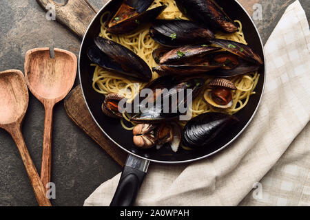 top view of delicious pasta with mollusks and mussels in frying pan on wooden cutting board near napkin and spatulas - Stock Photo