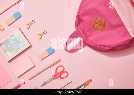 flat lay with pink school supplies and backpack isolated on pink