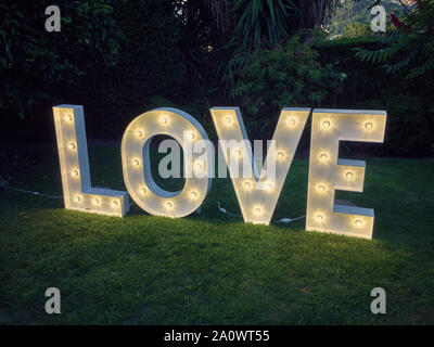 Wedding decoration: Letters saying LOVE in wood and light bulbs - Stock Photo